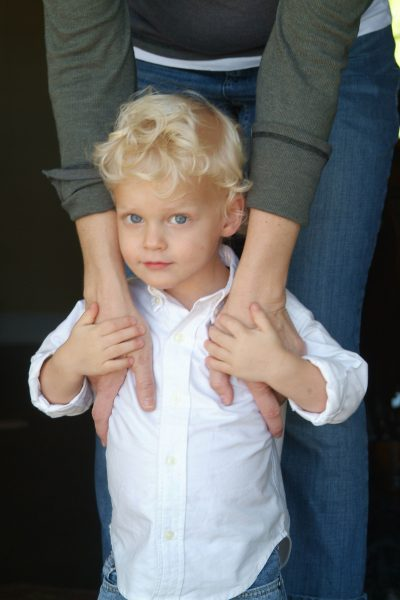 Outdoor Portrait of Young Boy with Mother's Hands