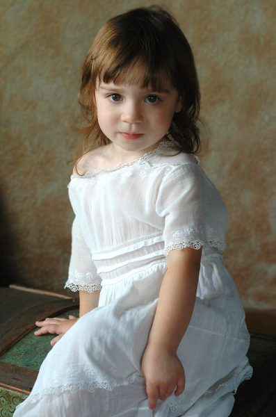 Studio Portrait of Young Girl in White Dress
