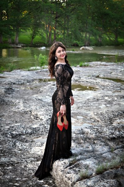 outdoor portrait of young woman in black with red shoes