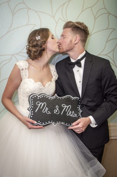 Bride & Groom kissing with sign