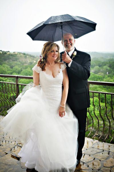 bride & groom with umbrella in the rain